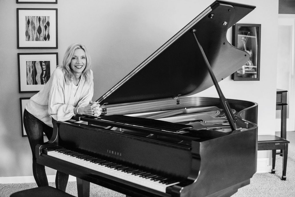 Adult women smiling and leaning on her piano
